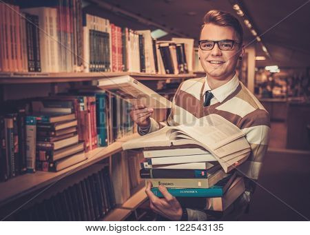 Young attractive librarian holding a pile of books in the university library.