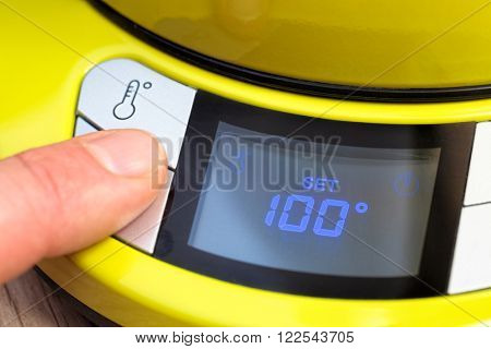 Finger pushing button on a digital thermostat control panel of electric tea kettle setting temperature to 100 degrees Celsius