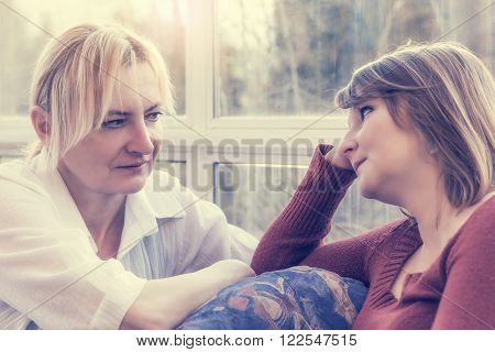 Middle age woman and young adult woman are sitting on the couch and they are facing each other with a serious look. Photo is edited as instagram effect.