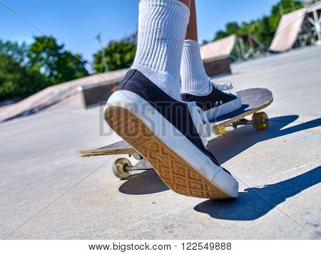 Legs wearing socks on skateboard close up in skatepark. Low section of skate.