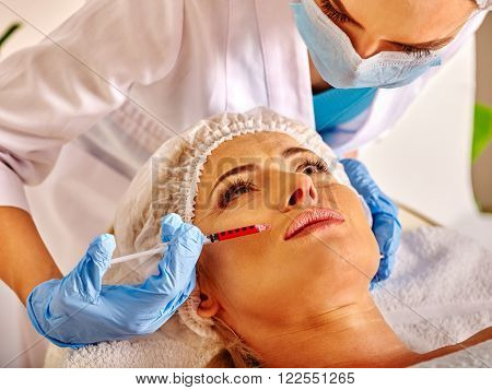 Woman looking up middle-aged in spa salon with beautician. Beauty female giving anti-age injections.