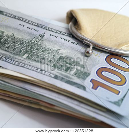 Bundle of US dollars banknotes sticking out of a small wallet still-life with selective focus