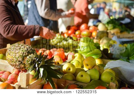 Closeup on person hand shopping for fresh food. Sale, consumerism concept and pineapple with fruits on grocery market stall background.