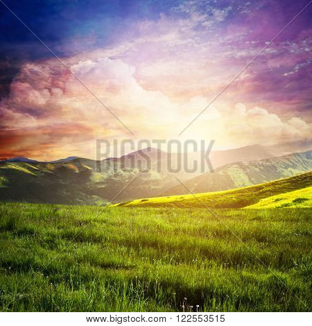 Fairtytale landscape with green grass, mountains, sunset fantastic sky. Summer adventure