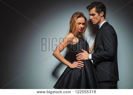 elegant couple in black posing together in black studio background. Man with hands on woman waist  is looking away while woman with hand on waist is looking down