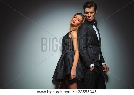 back to back elegant couple posing in gray studio background. man with hand in pocket looks away while woman leaning on man looks at the camera