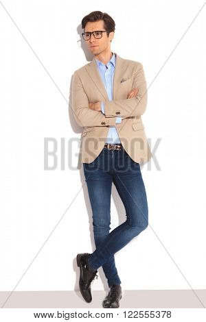 portrait of smart man wearing glasses posing in white studio background with hands and legs crossed, while looking away from the camera