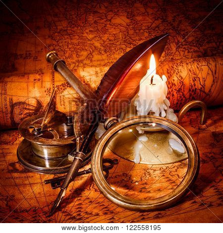 Vintage compass, magnifying glass, pocket watch, quill pen, spyglass lie on an old ancient map in 1565 with a lit candle. Vintage still life. poster
