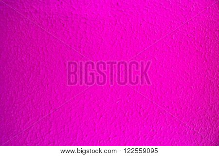 Bright pink knobbly painted wall texture close up in horizontal 3:2 format.