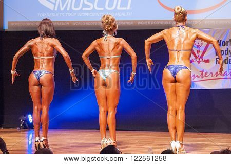 MAASTRICHT THE NETHERLANDS - OCTOBER 25 2015: Female fitness bikini models show their best back pose at championship on stageat the World Grandprix Bodybuilding and Fitness of the WBBF-WFF on October 25 2015 at the MECC Theatre in Maastricht