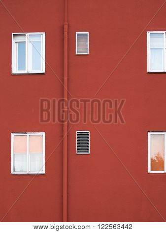 vertical architectural abstraction with red painted concrete wall with rectangular windows and bklymi frames ventilation grilles and the drain pipe
