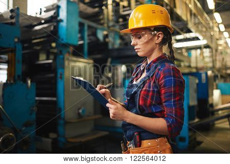 Young woman making notes in document in factory