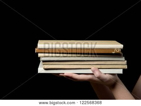 stack of book in a child's hand on a dark background
