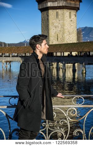 Handsome man standing near metal fence in Lausanne. Famous wooden bridge and Water Tower on background.