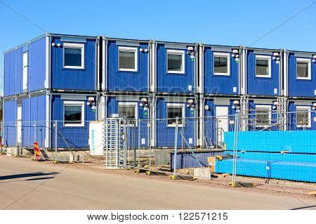 Kalmar Sweden - March 17 2016: Blue stackable modular work sheds or offices at a construction site. Fence and road in foreground.