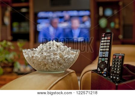 Ready to watch sports on TV with bowl of pop corn and remote
