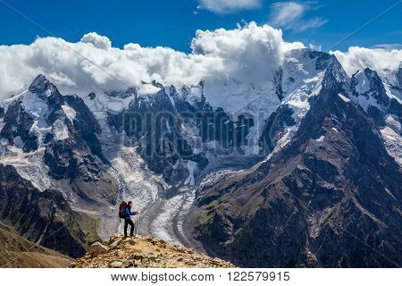 Man hiker in blue jacket with red backpack standing on cliff and enjoying view from top of mountain. Russia, Caucasus mountains