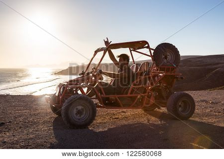 Active man driving quadbike on dirt road by the sea in sunset showing rocking sign to the camera.