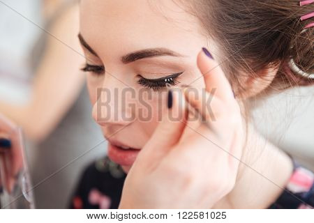 Closeup of makeup artist doing false lashes to young woman in curlers