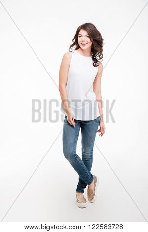 Full length portrait of a casual happy woman standing isolated on a white background