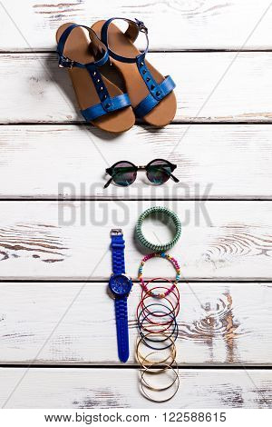 Female sandals and small accessories. Footwear and accessories on shelf. Woman's shoes for summer. Tiny good-looking accessories.
