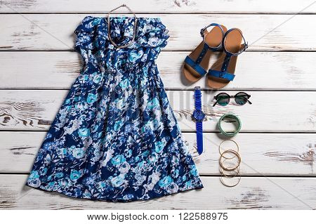 Woman's vintage dress and sandals. Vintage clothing on wooden background. Strapless dress with flower pattern. Vintage blue flower pattern.