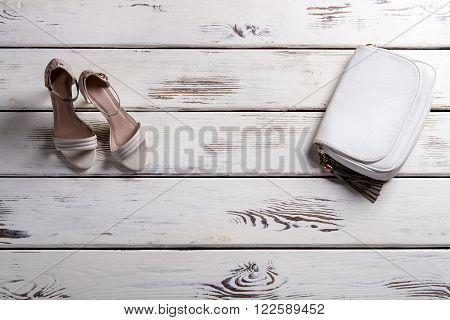 Lady's shoes and small purse. Showcase with footwear and purse. Leather purse and heel shoes. Elegant footwear and leather accessory.