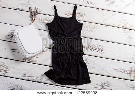 Black u-neck dress and purse. Dark dress on white shelf. Dark dress and white purse. Contrast of clothing and accessory.