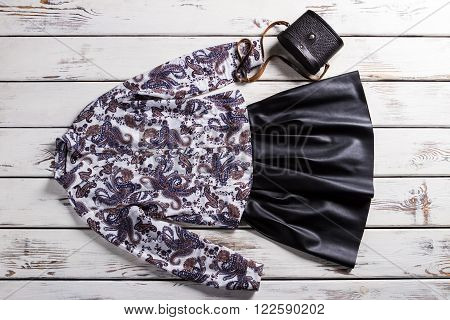 Black skirt with floral shirt. Elegant clothes on white table. Leather skirt and small purse. Retro-looking handbag and clothes.