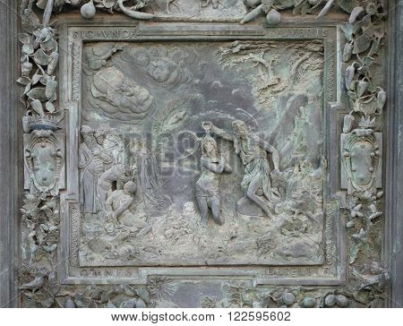 PISA, ITALY - JUNE 06, 2015: PISA, ITALY - JUNE 06, 2015: Jesus Christ's Baptism, sculpture work from Giambologna's school, left portal of the Cathedral St. Mary of the Assumption in Pisa, Italy