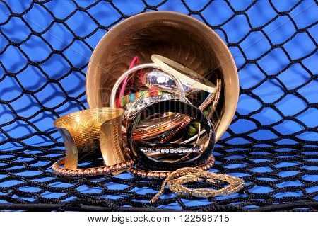 Brass bowl filled with multi styled bracelets and chains against a blue background and black netting.