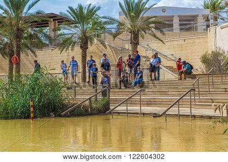 Jericho, Israel - October 27, 2015: Tourists near the Sacred water of the River Jordan. River where Jesus of Nazareth was baptized by John the Baptist. The border between Jordan and Israel