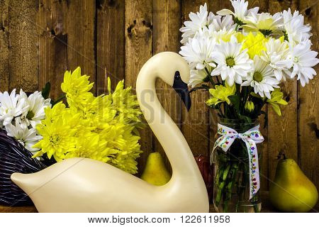 carved swan in front of fresh cut flowers in basket and glass jar on wood background