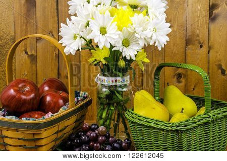 baskets of fruit and flower bouquet in glass mason jar on wood background