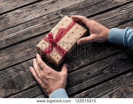 Gift box in man's hands. Top view.