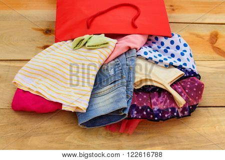 Women's clothing falls out of paper shopping bags on wooden background.