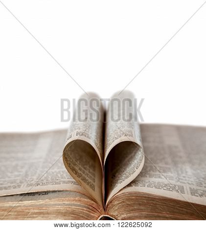 An old Bible opened with deliberate focus on the edges of the heart-shaped folded pages and copy space. Shallow depth of field to prevent copyright issues. Isolated on White.