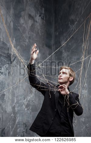 Young man in a black suit got caught in the web.