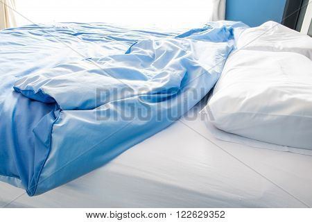 Unmade bed with white pillow and messy ** Note: Shallow depth of field