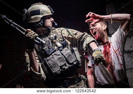 KIEV,UKRAINE - February 20 : Actor in a zombie costume with a bloody face biting a soldier in uniform during a thematic game about zombies in Kiev,Ukraine on February 20,2016.