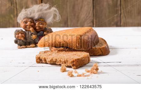 The group of fantastic beings brownie looks at a piece of bread. Against old gray boards bread a rye close up small depth of sharpness