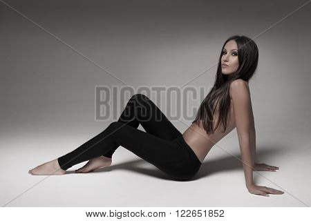 Gorgeous young woman posing in studio wearing black leggings.