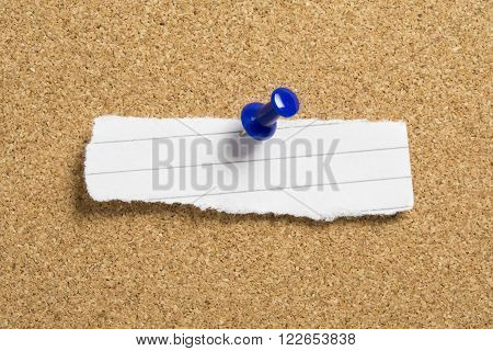 Blank torn paper with blue push pin on a cork board