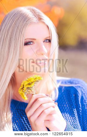 Attractive smiling woman 20-25 year old with dandelions outdoors. Looking at camera. Young adults. 20s. Spring season.