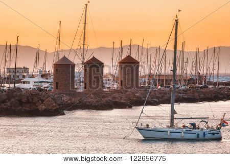 The yacht on the background of the mills in the Mediterranean harbor Mandraki. Rhodes Island. Greece