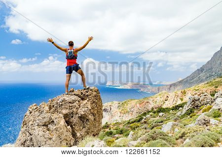 Success achievement running or hiking accomplishment or business concept man celebrating with arms up raised outstretched trekking climbing trail running outdoors. Motivation and inspiration looking at beautiful landscape view.