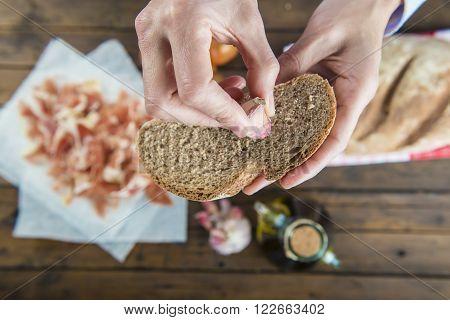 Chef Rubbing Garlic On A Bread Slice