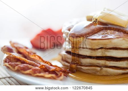 Pancakes with butter and honey served with bacon and strawberries
