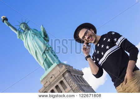 Tourist standing under the Statue of Liberty in New York making a phone call