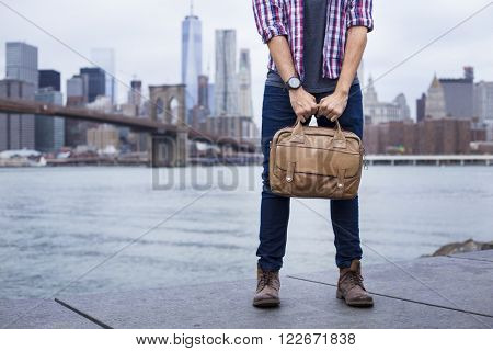Closeup of a young entrepreneur with boots and a briefcase in New York